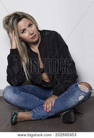 Young woman in a jeans sitting on the floor near white wall.