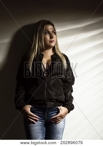 Young woman in a jeans standing near white wall on a striped shadow.