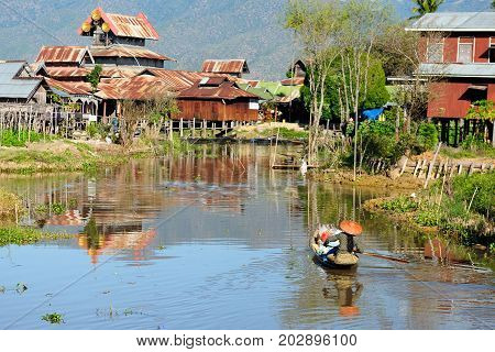 Ancient houses and their reflection and boat sailing between them in the water on the Inle Lake Myanmar