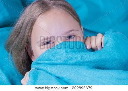 Beautiful young girl lying down in the bed and sleeping. Teen girl with open eyes covers her face with blue blanket in the morning. Do not get enough sleep concept. Copy space