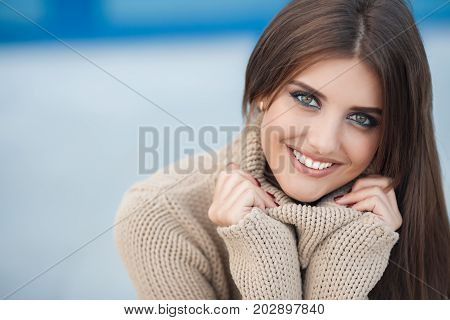 Young beautiful woman brunette with long straight hair and gray-green eyes,a nice smile and white straight teeth,light makeup,dressed in a beige sweater and blue jeans,hanging out in the city in the spring,sitting on the steps,one in the fresh air