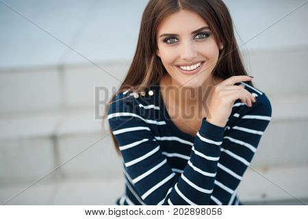 Young beautiful woman brunette with long straight hair and gray-green eyes,a nice smile and white straight teeth,light makeup,dressed in a striped t-shirt and blue jeans,spends time in the city in the spring,sitting on the steps,one in the fresh air