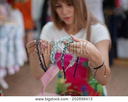 A young woman in a shop choosing hair hoops, hair bands on a light gray blurred background. Shopping, shop, accessories, beautiful concept.