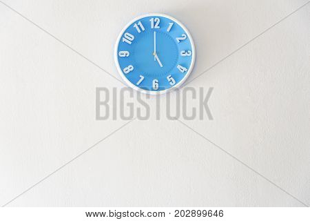 Good afternoon or after midnight with 5:00 clock on white concrete wall interior background with copy space message board concept. 5 pm is a coffee break time in the afternoon. 5 am is the late night