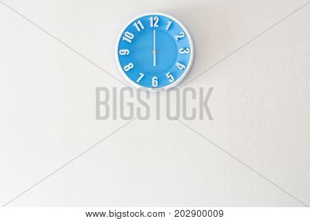 Good morning or evening time with 6:00 clock on white concrete wall interior background with copy space message board concept. Good morning or evening is the greeting in the morning and evening