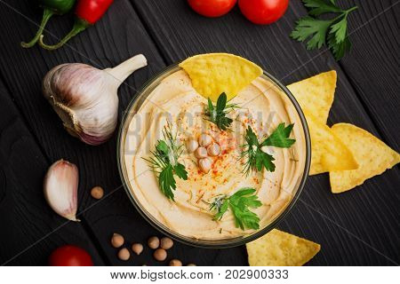 A view from above on a glass bowl full of nutritious hummus made of chickpea, close-up. Arabic dish surrounded by tomatoes, garlic, chickpea, and gold nachos on a black wooden background. Copy space.