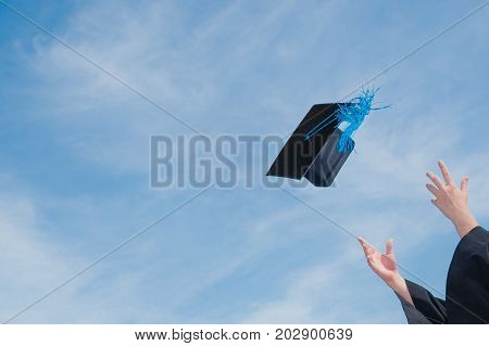 Graduate success celebration throw graduation cap in the sky concept background with copy space
