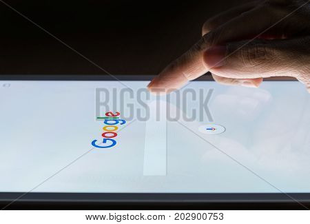 BANGKOK THAILAND - FEBRUARY 19 2017: A man's hand is touching screen on smart device at night for searching on Google search engine. Google is the most popular Internet search engine in the world.