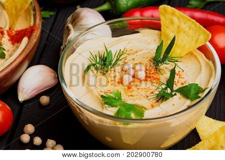 A close-up picture of a glass bowl with nutritious hummus decorated with chickpea and yellow nachos. Arabic dish surrounded by a garlic, red hot chili pepper, and gold nachos on a black background.