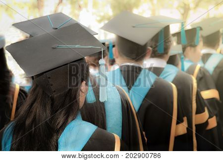 Selective focus on bachelor degree woman graduates in commencement graduation ceremony row metaphor education success concept background