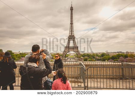 Tourists Watch And Photograph The Eiffel Towe