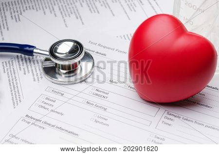 close up stethoscope red heart beaker and patient information form on desk heart healthcare technology medical diagnosis medical report record and history patient concept selective focus