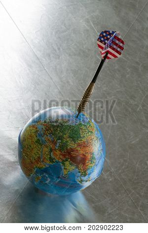The globe pierced by an arrow on a scratched surface