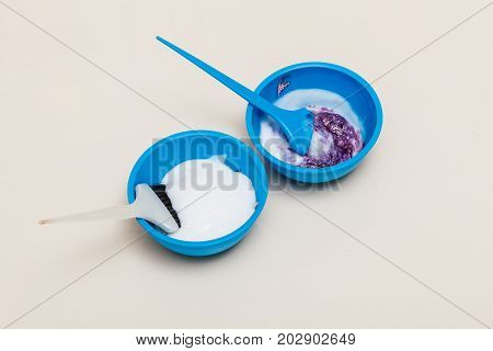 Hair dyeing at home or in hairdresser salon concept. Two blue plastic bowls with bleach hair dye and brush