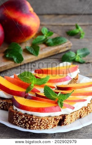 Light sandwiches with cream cheese, nectarines and mint on a serving plate and on a vintage wooden table. Healthy sandwich recipe for kids. Vertical photo