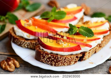 Sandwiches with cream cheese, nectarines, walnuts and mint on a serving plate and on an old wooden table. Healthy sandwiches idea. Closeup