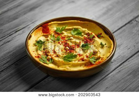 Close-up picture of a beautiful hummus dip in a big ceramic bowl on a blurred wooden background. Hazelnuts, greens and hot pepper on a traditional spicy hummus spread with eggs and olive oil.