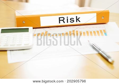 Orange binder on desk in the office with calculator and pen