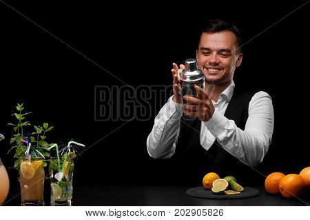 A bar counter with different cocktails with leaves of mint, lemon, lime, oranges, a bartender wipes a shaker on a black background. Party, cafe, restaurant, night club, concept.