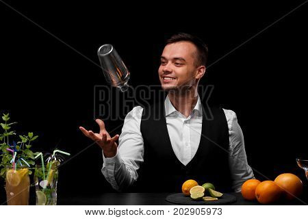 A bar counter with different cocktails, lemon, lime and oranges, a bartender tosses up a shaker on a black background. Party, night club, cafe, restaurant, concept.