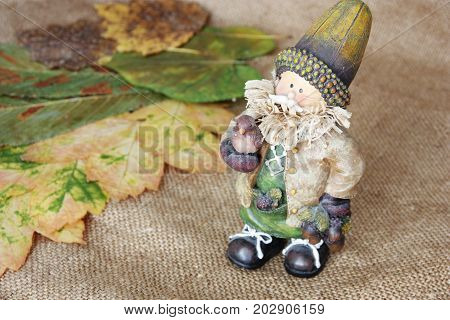wooden man on burlap amid dried autumnal leaves