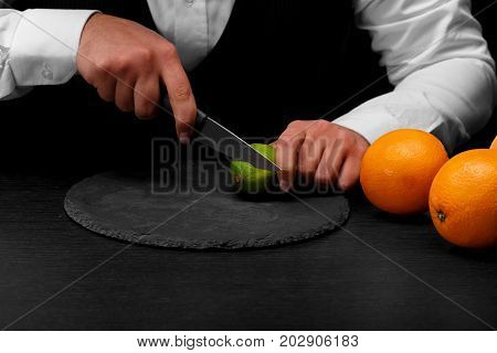 A bar counter with sappy bright oranges, a bartender slices a sappy green lime with a knife on a black background. Night clubs, restaurant, cafe, party, concept.