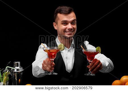 A bar counter with a metal shaker, oranges, lemon, a smiling bartender with two margarita glasses on a black background. Party, night club, cafe, restaurant concept.
