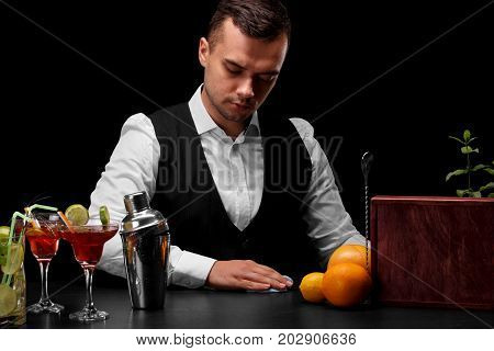 A charming bartender wipes a bar counter, bright juicy oranges, lemon, a metal shaker, margarita glasses on a black background. Night club, cafe, restaurant, party concept.