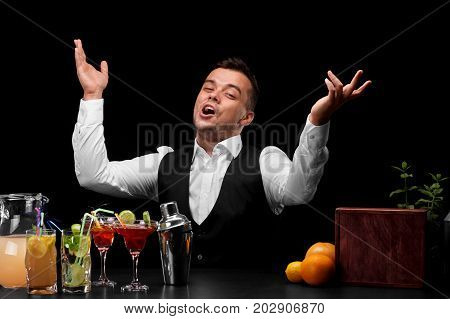 A smiling bartender, a bar counter with oranges, lemon, margarita glasses on a black background. Party, cafe, restaurant, night club concept.