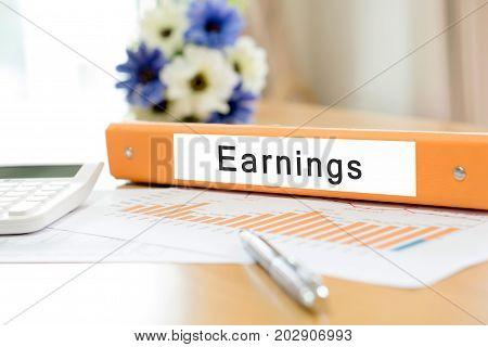 Orange binder debtor on desk in the office with calculator and pen