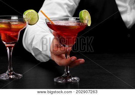 Margarita glasses with slices of lime on a bar counter holds a bartender on a dark blurred background. Party, night club, entertainment concept.