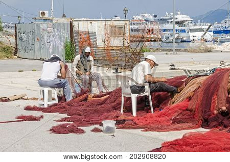 Corfu Greece - June 7 2017: Fishermen repairing their colorful nets in a port of Corfu