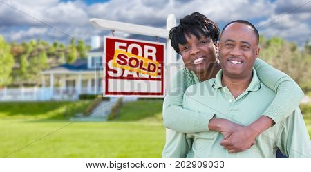 Happy African American Couple In Front of Beautiful House and Sold For Sale Real Estate Sign.