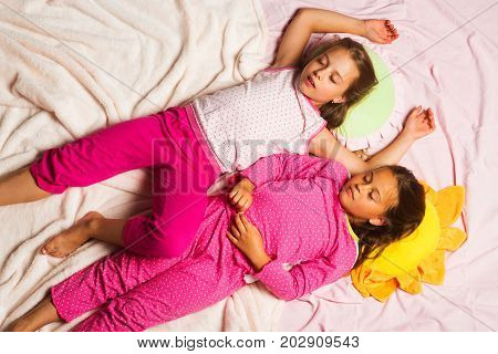 Children With Sleepy Faces Lie Close On Pink Blanket Background
