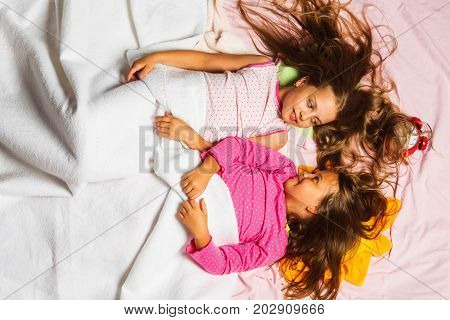 Kids In Pink Pajamas Covered With White Blanket.