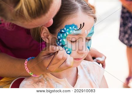 Funny face art painting, artist makes child makeup. Blue butterfly drawing. Children event, birthday party and modern creative entertainment.
