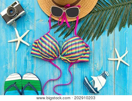 Summer Fashion woman big hat and accessories camera and sunglasses go to travel in the beach. Tropical sea.Unusual top view blue background. Summer Concept.