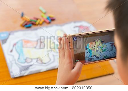 ZhongshanChina-August 29 2017:kid playing Augmented Reality popup paintings of a color filled elephant via mobile. AR and VR games become more and more popular.