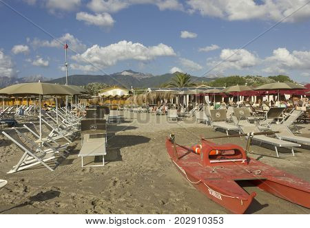 MARINA DI MASSA, ITALY - AUGUST 17 2015: Bathing establishment in Marina di Massa with rowing life boat overlooking the Apuan Alps