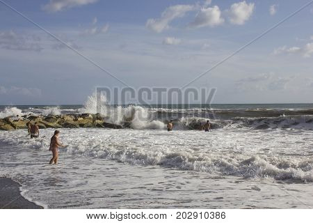 MARINA DI MASSA, ITALY - AUGUST 17 2015: People bathing in rough seas near the rock in Marina di Massa Tuscany Italy