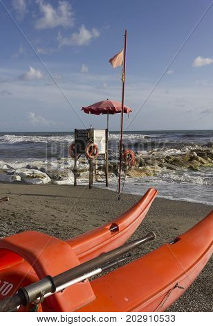 MARINA DI MASSA, ITALY - AUGUST 17 2015: Lifeguard tower and rowing boat on the shoreline with rough seas nobody around