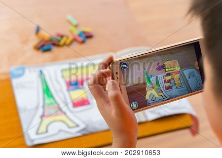 ZhongshanChina-August 29 2017:kid playing Augmented Reality popup paintings of the filled Arch of Triumph & Eiffel Tower via mobile. AR and VR games become more and more popular.
