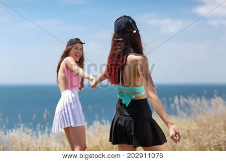 Two laughing beautiful girls in swimsuits strolling on a seashore on a blurred natural background. Weekends, vacation, rest, relaxation, holiday concept.