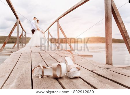 Fashionable bride shoes on the dock. Silhouette of the bride and groom in the background. Beautiful sunset on a wedding evening. Wedding background with free place for text.
