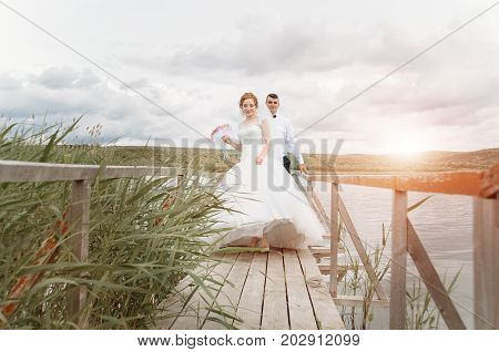 Young wedding couple enjoying romantic moments outside next to the pier on a summer meadow. Wedding background with free place for text.