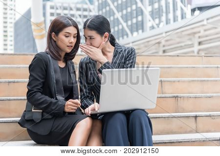 Business women gossip while using laptop at outdoor. Business and coworker concept