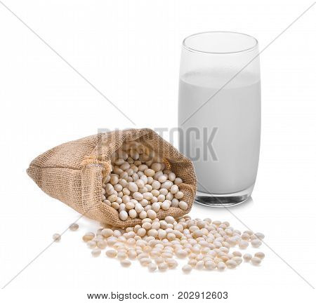 small white beans haricot white pea white kidney in a bag sackcloth with hot milk in a glass isolated on white background