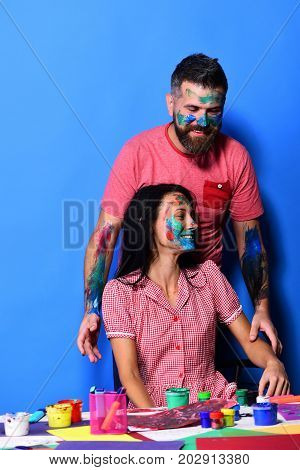 Man and woman with happy face expression by desk with paints. Body art and craft concept. Couple in love with faces painted with gouache on blue background. Artists family by table with art supplies