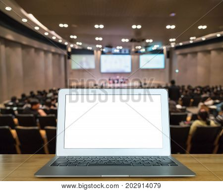 Computer laptop on the wood table over Abstract blurred photo of conference hall or seminar room with attendee background Business and education meeting concept