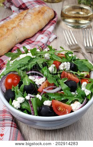 Variation of Greek salad with arugula cherry slices feta and olives